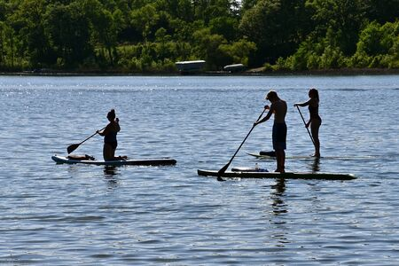 Three unidentified individuals are silhouetted in a lake while using paddle boards. Stock fotó
