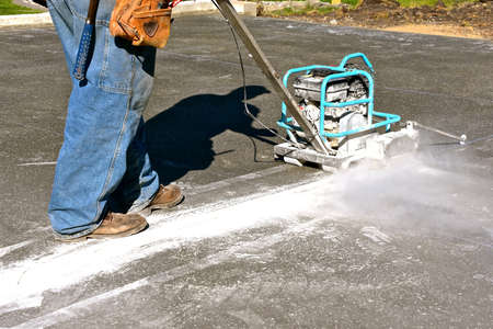 A cement cutter is cutting expansion joints on recently poured concrete floor of a building stite 版權商用圖片