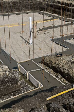 The basement footing of a new house site with reinforcing rods protruding.