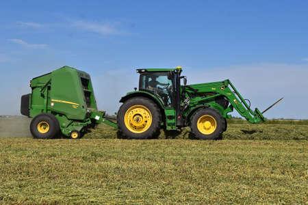 MOORHEAD MINNESOTA, 2. Juni 2020: Der John Deere-Traktor und die Rundballenpresse sind Produkte von John Deere Co, einem amerikanischen Unternehmen, das Landwirtschaft und Bauwesen herstellt