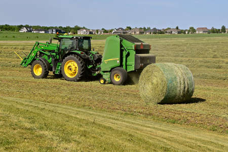 MOORHEAD MINNESOTA, June 2, 2020: The John Deere tractor and baler harvesting hay next to a new housing development are products of John Deere Co, an American corporation that manufactures agricultural and construction