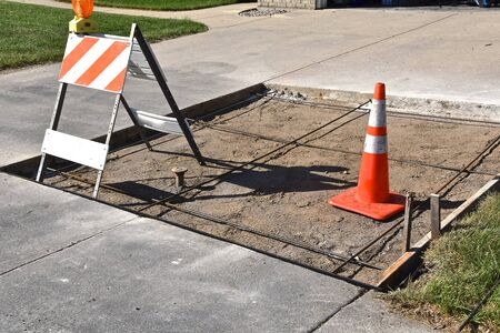 A section of a driveway is being repaired on a residential home with warning cones displayed. 版權商用圖片