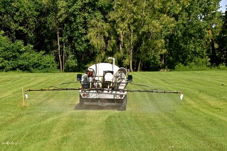 A truck with a tank full of liquid spray and extended booms is spraying a grassy meadow for weeds. 版權商用圖片