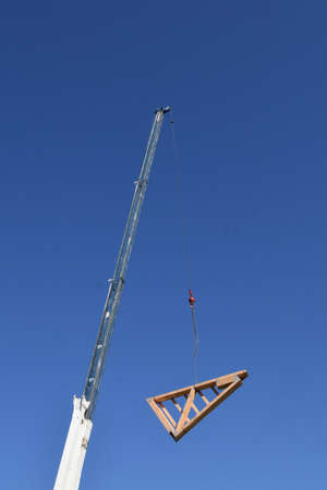 Pre-built rafterstrusses are being lifted by a cable and boom to be placed on top of a wooden framed building under construction.