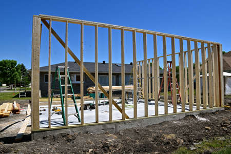 Half of the walls of a garage under construction have been framed.