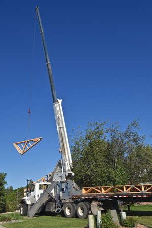 Pre-built rafters and trusses are being lifted by a cable and boom to be placed on top of a wooden framed building under construction. 新聞圖片