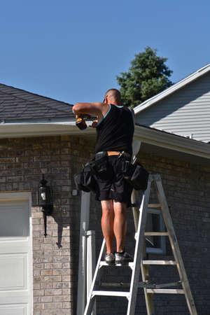 Unidentified worker repairing gutters on a house 新聞圖片