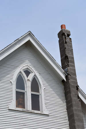 The  block chimney of an old white church has fallen into disrepair