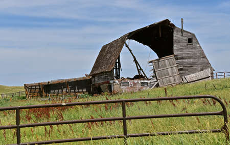A metal gate blocks off a crumbling old hip roofed barn