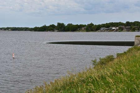A horseshoe shaped dam sends reservoir water down a spillway.