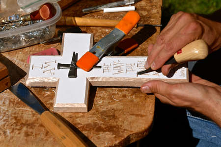 A chisel carver works on a cross shaped piece of wood with the word of a Bible verse. 免版税图像 - 151134082