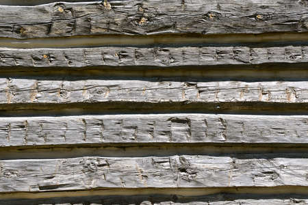 The weathered hewn gray logs of an old cabin create parallel lines.