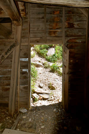 View from the inside of an old mining building to an open doorway.