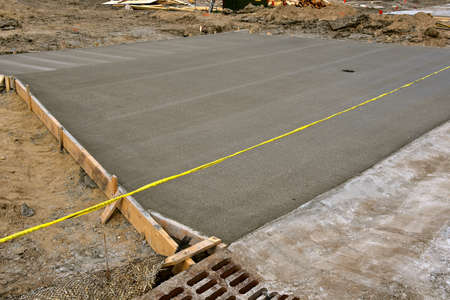 Freshly poured concrete is curing on the front portion of a driveway under construction.