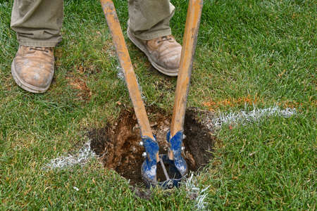 A hand powered hole digger is used to dig a hole for a post of a new backyard fence