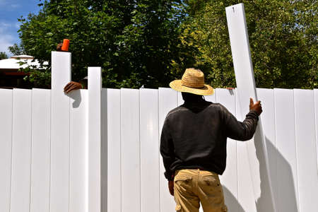 The rail, posts, and slats are being assembled on a new outdoor vinyl privacy fence.