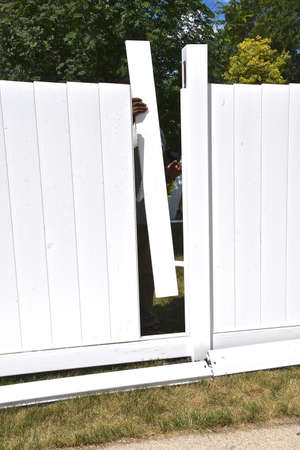 The rail, posts, and slats are being assembled on a new outdoor vinyl privacy fence. Stockfoto