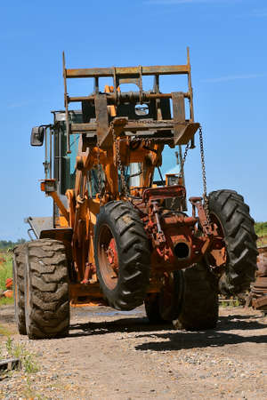A huge fork lift with long times carries an old junked tractor as it hangs from chains.