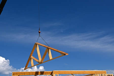 A boom and cable transfer a load of pre-made rafters and trusses to the top of a building under construction. Reklamní fotografie