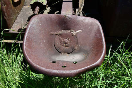 An old tractor seat is full of rust and has holes holes rain drainage.