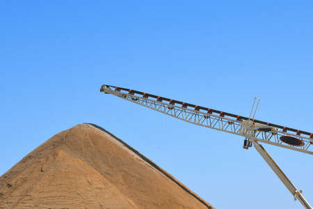 A conveyor belt which drops sand creating a hug e pile for construction projects