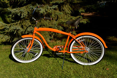 A bright orange retro styled  bicycle is parked by the evergreen trees.