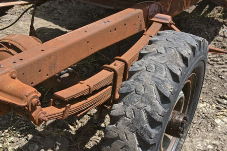 The spring assembly of an old rusty pickup is attached to the chassis and axle with a bald snow tire. Stock Photo