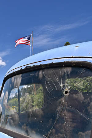 A bullet hole in an old truck window  on the drivers side shatters the area with the American flag flying in the background.