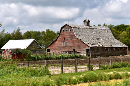 An old red rickety hip roofed dairy barn is in a state of deterioration. 免版税图像