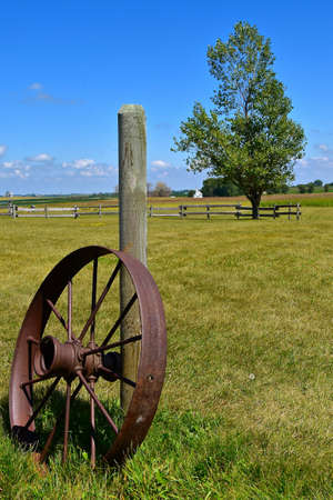 An old steel wheel for an antique machinery leans against a wooden post in a grassy meadow.