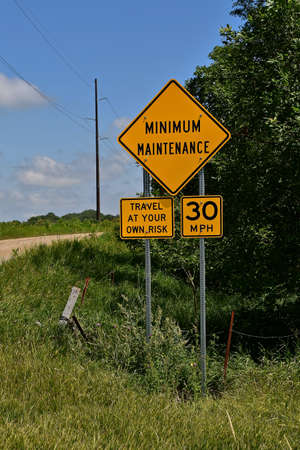 A rural minimum maintenance road posts a sign enforcing the speed limit at 30 mph.