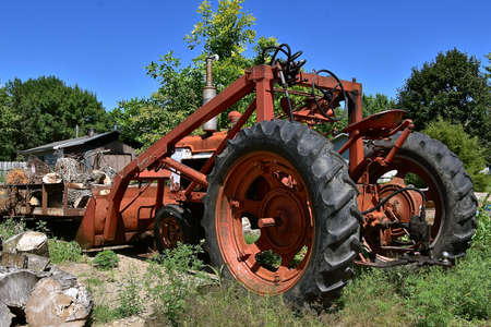 HURON, SOUTH DAKOTA, August 5, 2020:  The old Farmall tractor parked by a woodpile is a model name and later a brand name for tractors manufactured by the American company International Harvestor.