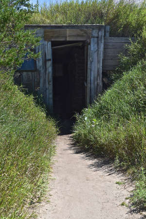 A path leading to then doorway of a dugout root cellar used by pioneers for keeping canned good s and food products cool in the hot seasons. 免版税图像