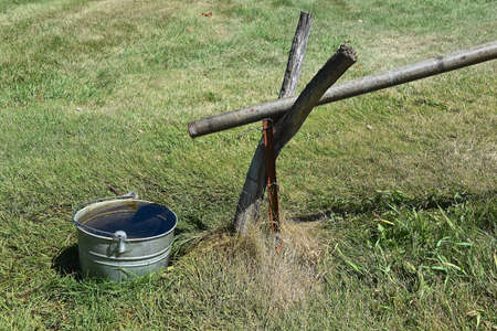 A hand-operated water pump with long handle bring water from a deep well and sends it down a pipe.