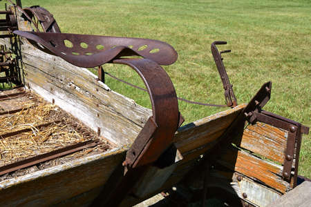 Old rusty seat of an old steel wheeled manure spreader pulled by horses