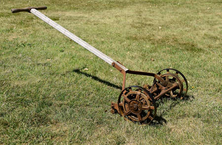 An old push lawn mower where the wheels and blades turn with the wheels.