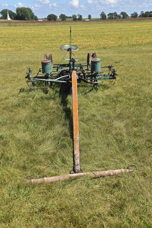 A long wooden hitch with a n attached metal singletree is attached to an old horse drawn corn planter with a seat for the operator Banco de Imagens