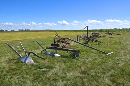 Very old pioneer horse pulled farm equipment is lined up in a row out on the prairie. Banque d'images