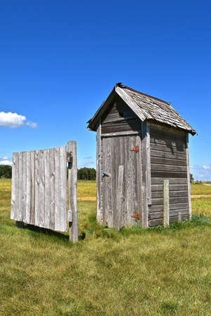 An old outhouse constructed from weathered wood with a front privacy fence
