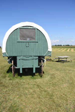 A portable covered wagon on wheels serves as a bunkhouse in a rural park camping setting. Stock fotó