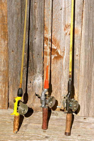 Three old retro spinning rod and reels lean against weathered fence boards Archivio Fotografico