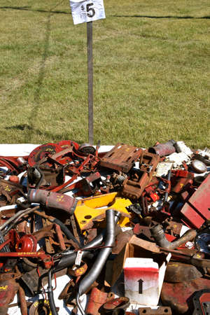 A pile of tractor and machinery parts are available for purchase at $5 each at a farm flea market.