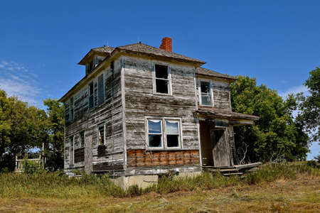 An old rural square home stands in disrepair in the rural countryside.