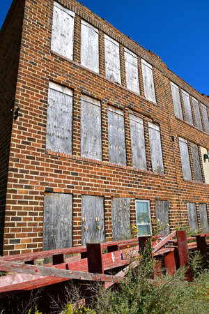 An old abandoned brick schoolhouse with boarded up windows is left to deteriorate into ruins.