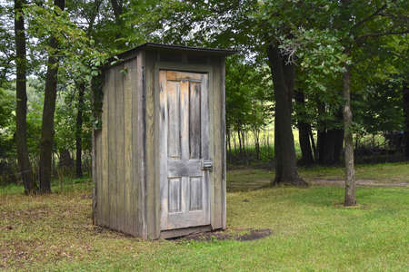 An outdoor outhouse is available in a a park setting Standard-Bild