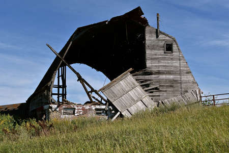 A very old barn is rotting and in a state of disrepair bringing back memories of a past dairy farm. Standard-Bild