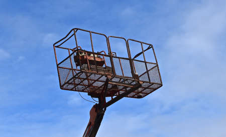An attached safety basket to a hydraulic lift for reaching high places is silhouetted against the blue sky.