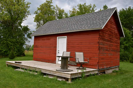 An old red granary is converted into a a summer shanty with a deck with several lounge chairs.