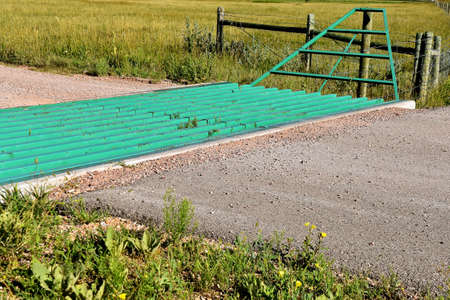 A metal grated cattle guard crossing on a western prairie driveway Stockfoto