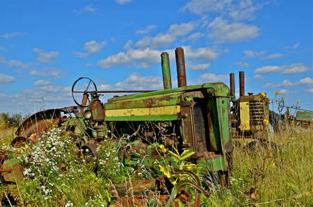 Several old tractors are surrounded by tall grass and weeds in a junkyard Redakční